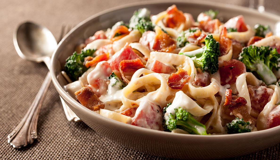 Image of fettucine alfredo with broccoli bacon and tomatoes in a bowl with fork and spoon on the left