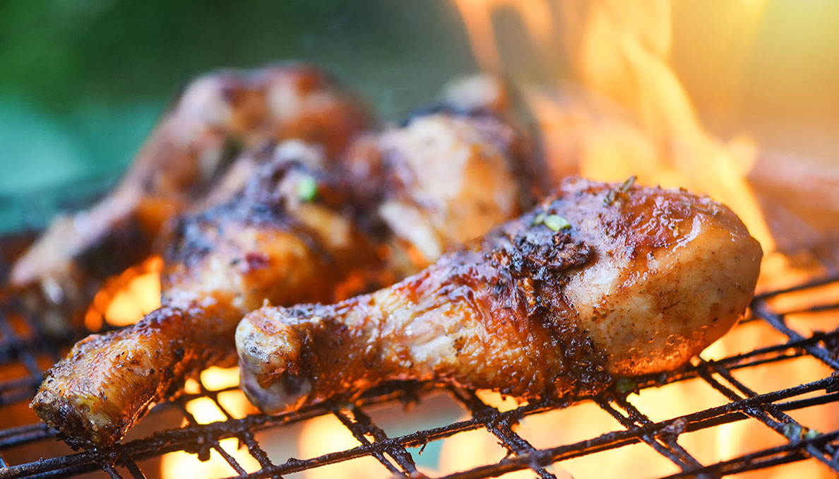 Image of chicken legs on a grill with Redneck Riviera 1776 BBQ Sauce