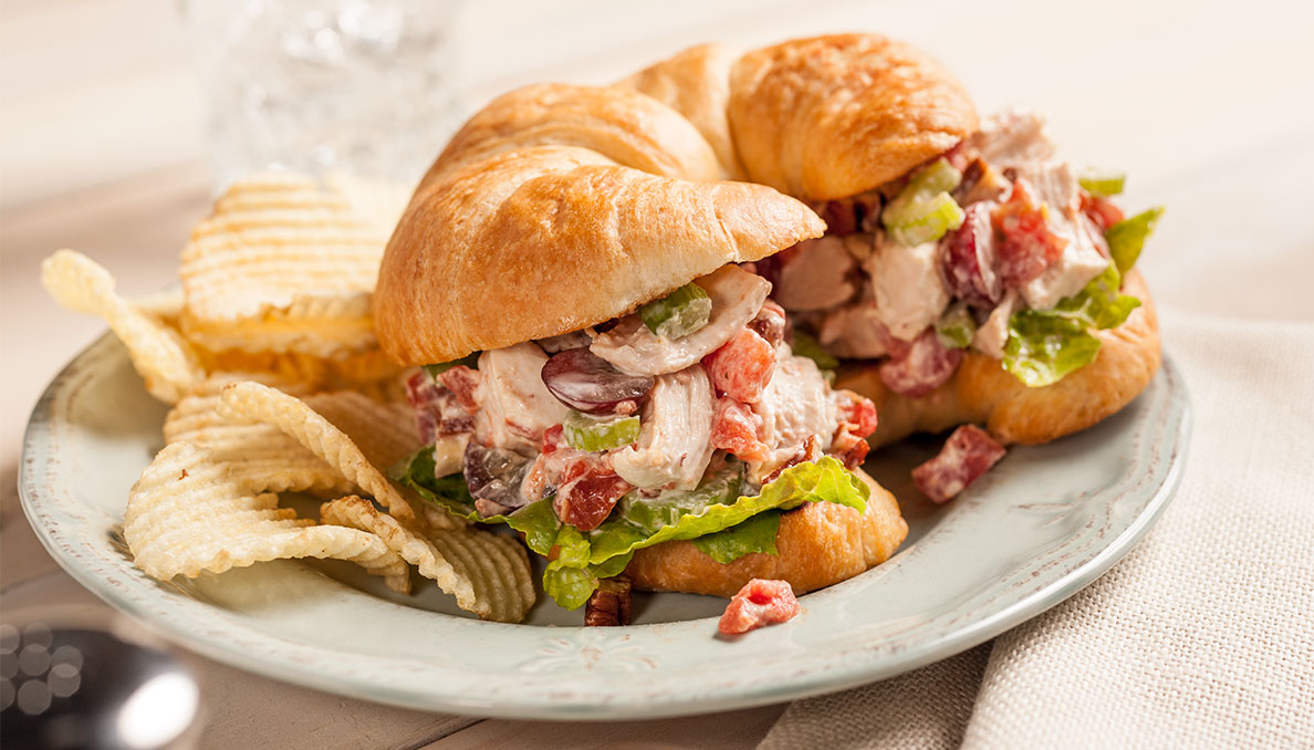 Image of Sassy Chicken Salad sandwich chicken salad with grapes celery diced canned tomatoes and chicken on a croissant