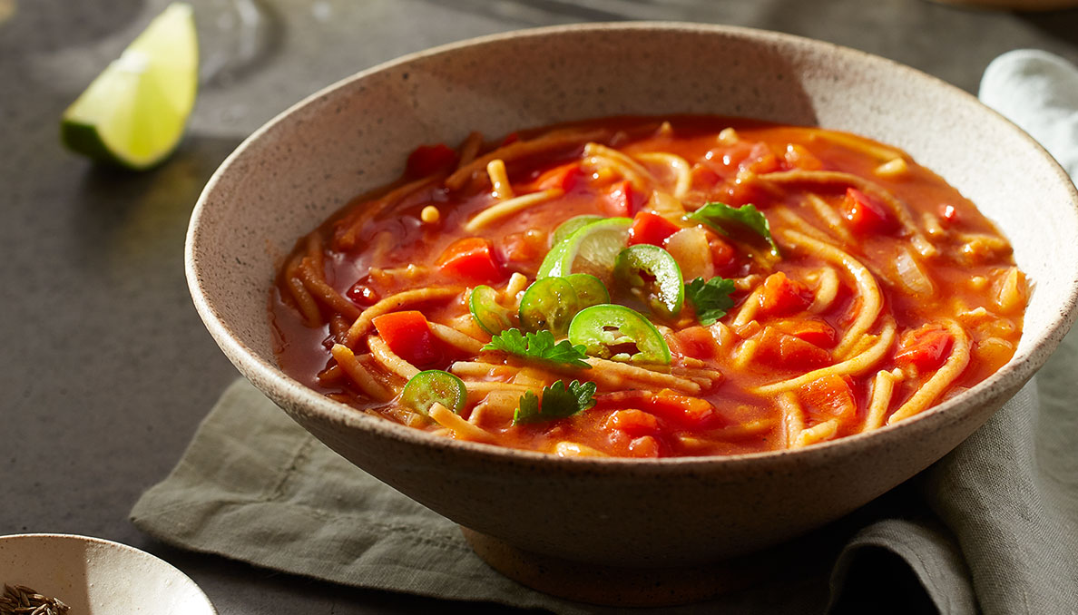 Straight on image of fideo soup with tomato base diced tomatoes noodles jalapeno slices and lime wedges